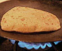 Cooking chapati on hot iron tava