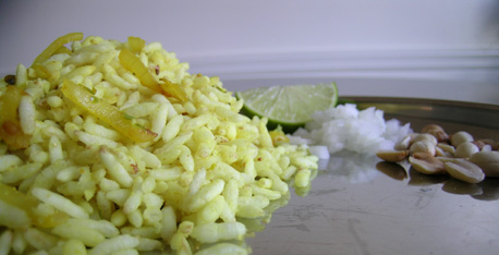 Buggani (puffed rice or murmura upma)  - On the side a lemon wedge, onions and roasted peanuts.