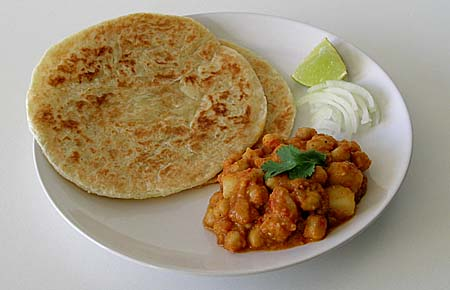 Paratha, Chole with Potatoes (aloo Chole), Lime wedge and finely chopped onions