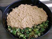 Covering sautéed okra with cornbread batter