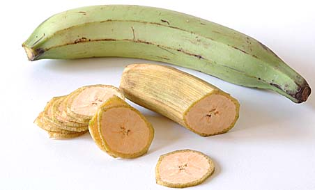 Plantain with outer skin peeled and sliced into thin round chips and whole Plantain