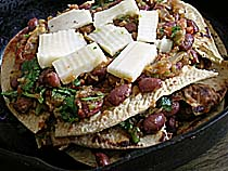 Layering Chapati pieces, Tomato, chutney, red beans and cheese in an iron skillet